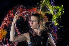 Donna moderna che è spruzzata con acqua variopinta Immagine Stock