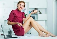 Donna moderna di affari che si siede sullo scrittorio funzionante all'ufficio immagine stock