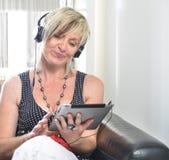 Donna moderna senior che risiede nel sofà con la compressa e l'Au elettronici Fotografia Stock Libera da Diritti