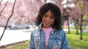 Donna multirazziale che ascolta la musica in un parco alla primavera archivi video