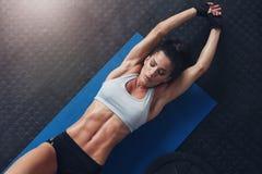 Donna muscolare che fa allungando allenamento sulla stuoia di esercizio Fotografia Stock Libera da Diritti