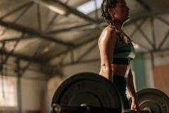 Donna muscolare che fa gli esercizi pesanti Fotografia Stock Libera da Diritti