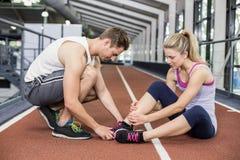 Donna muscolare che ha una ferita alla caviglia Immagine Stock