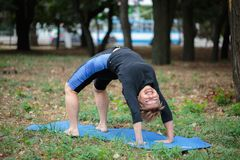 Donna muscolare che risolve su uno sfondo naturale Forte donna anziana di yoga Concetto duro di yoga Fotografia Stock Libera da Diritti