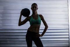 Donna muscolare che tiene una palla medica Immagini Stock