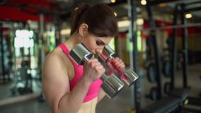 Donna muscolare dell'atleta in una cima rosa che risolve nei pesi di sollevamento della palestra Ragazza di forma fisica che si e video d archivio