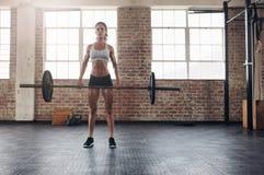Donna muscolare in una palestra che fa gli esercizi pesanti Fotografia Stock Libera da Diritti