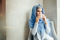 Donna musulmana abbastanza giovane con una tazza di caffè o tè nell'azione Fotografia Stock Libera da Diritti