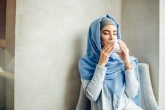 Donna musulmana abbastanza giovane con una tazza di caffè o tè nell'azione Immagine Stock Libera da Diritti