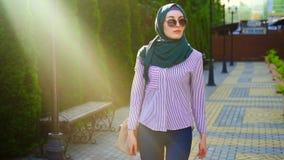 Donna musulmana alla moda in hijab e vetri, sunflare Mo lento video d archivio