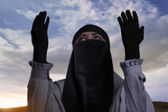 Donna musulmana asiatica religiosa con hijab che solleva mano e pregare Immagini Stock