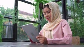 Donna musulmana asiatica sorridente dei bei giovani che utilizza compressa che si siede nel salone a casa Godendo del tempo nel p stock footage