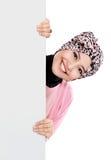 Donna musulmana attraente felice che tiene bordo bianco in bianco Immagine Stock Libera da Diritti