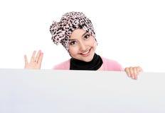 Donna musulmana attraente sorridente che tiene bordo bianco in bianco Immagine Stock Libera da Diritti