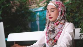 Donna musulmana in caffè che lavora all'affare con il computer portatile stock footage
