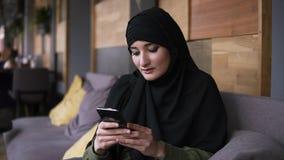 Donna musulmana in caff? facendo uso del suo smartphone, media sociali di chiacchierata di lettura rapida online che dividono sti stock footage
