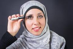 Donna musulmana che applica mascara immagine stock