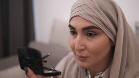 Donna musulmana che fa contorno sul suo occhio facendo uso del eyepencil nero Vita moderna della gente musulmana Vista frontale d video d archivio