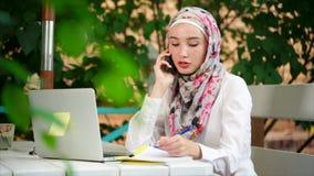 Donna musulmana che ha conversazione di affari sul cellulare stock footage