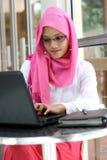 Donna musulmana che per mezzo del computer portatile Fotografia Stock