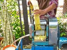 Donna musulmana che per mezzo del mulino a cilindri per estrarre il succo della canna da zucchero Fotografia Stock Libera da Diritti