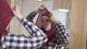 Donna musulmana che porta una sciarpa davanti ad uno specchio stock footage
