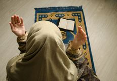 Donna musulmana che prega per il dio musulmano di Allah alla stanza vicino alla finestra Mani della donna musulmana sul tappeto c Fotografia Stock