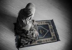Donna musulmana che prega per il dio musulmano di Allah alla stanza vicino alla finestra Mani della donna musulmana sul tappeto c Immagini Stock Libere da Diritti
