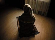 Donna musulmana che prega per il dio musulmano di Allah alla stanza vicino alla finestra Mani della donna musulmana sul tappeto c Fotografia Stock Libera da Diritti