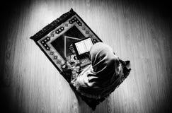 Donna musulmana che prega per il dio musulmano di Allah alla stanza vicino alla finestra Mani della donna musulmana sul tappeto c Immagine Stock
