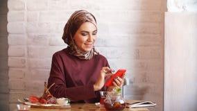 Donna musulmana di affari che lavora al telefono cellulare in caffè archivi video