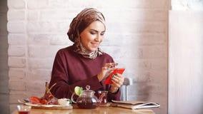 Donna musulmana di affari che lavora al telefono cellulare in caffè video d archivio