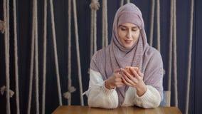Donna musulmana felice che per mezzo dello smartphone archivi video