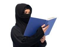 Donna musulmana in libro di lettura del hijab sopra bianco Fotografia Stock