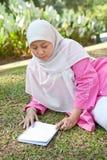 Donna musulmana matura che gode della sosta con un libro Fotografia Stock Libera da Diritti