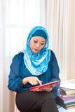 Donna musulmana matura con un libro in centro espositivo fotografia stock libera da diritti