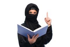 Donna musulmana nel hijab con il libro sopra bianco Immagine Stock