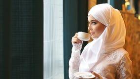 Donna musulmana in un vestito da sposa bianco con una tazza di tè in sue mani archivi video