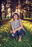 Donna naturale che posa con gli alberi in lampadina soleggiata, retro filtro Immagini Stock