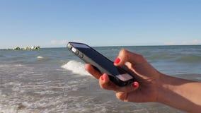 Donna negli sms del bikini che mandano un sms facendo uso del app sullo Smart Phone alla spiaggia Primo piano delle mani facendo  stock footage