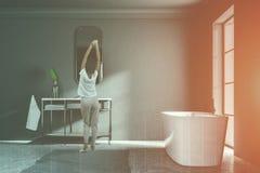 Donna nel bagno grigio del sottotetto, vista laterale della vasca del lavandino Immagini Stock