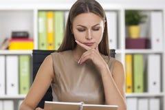 Donna nel beige che legge una nota immagine stock