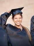 Donna nel bordo del mortaio della tenuta dell'abito di graduazione sopra Immagini Stock Libere da Diritti
