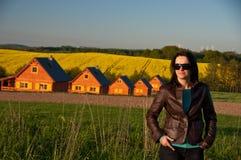 Donna nel campo dalle case Fotografie Stock Libere da Diritti