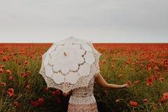Donna nel campo del papavero con l'ombrello Sguardo nostalgico vago Immagine Stock