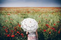 Donna nel campo del papavero con l'ombrello Sguardo nostalgico vago Fotografia Stock
