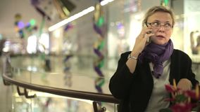 Donna nel centro commerciale che parla sul telefono stock footage