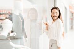 Donna nel centro commerciale La ragazza sta stando vicino alla finestra di deposito che esamina il nuovo vestito immagine stock