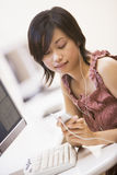Donna nel centro di calcolo che ascolta il giocatore MP3 Fotografie Stock Libere da Diritti