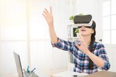 Donna nel cercare della cuffia avricolare di realtà virtuale Immagini Stock